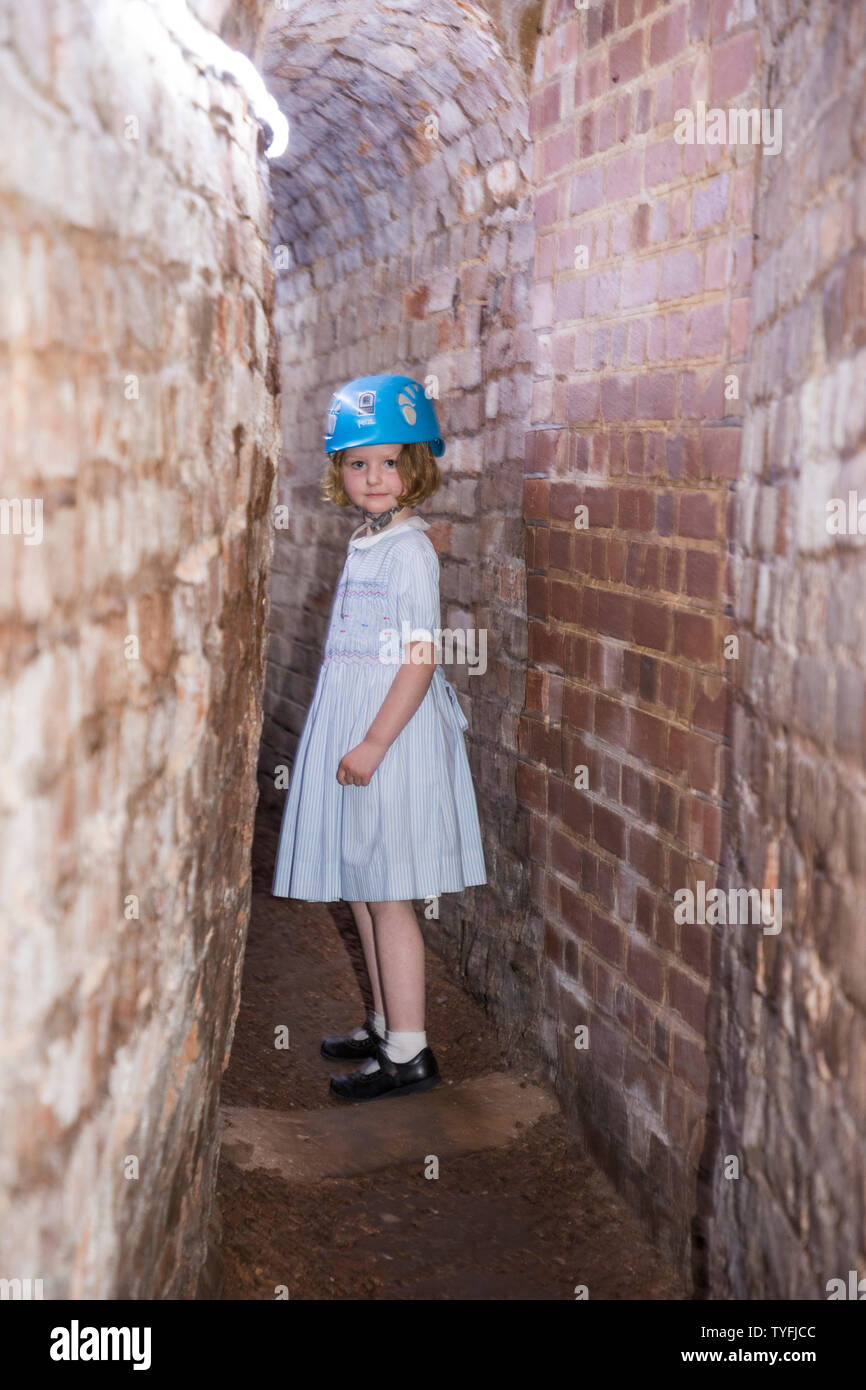 Tour including kid / kids and young tourist girl follow a group trip around Exeter's underground passages and tunnels, interesting destination for family tour of these ancient cut and cover tunnel network. UK (109) - Stock Image