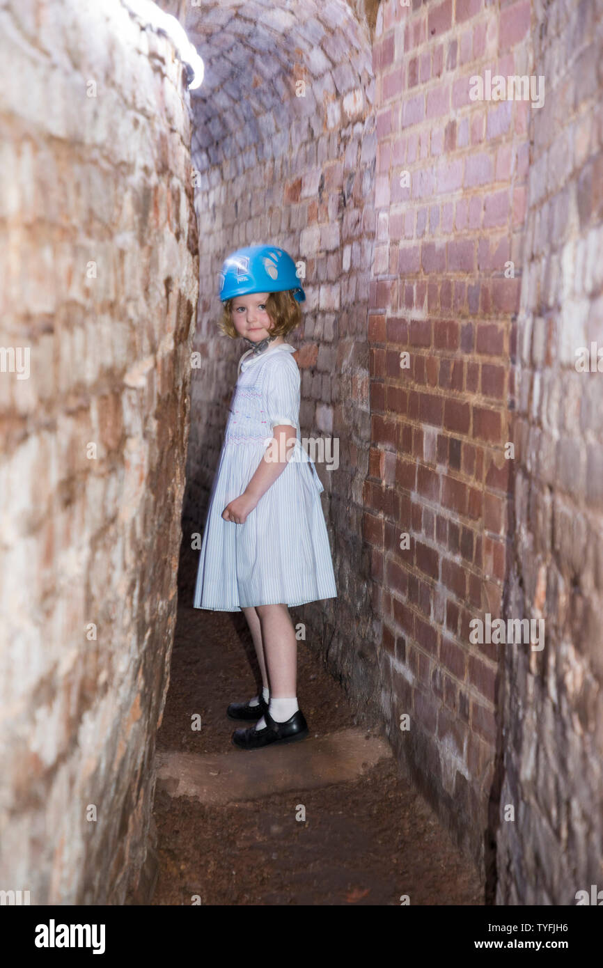 Family including children / kid / kids and young girl follow a group trip around Exeter's underground passages and tunnels, interesting destination for family tour of these ancient cut and cover tunnel network. UK (109) - Stock Image