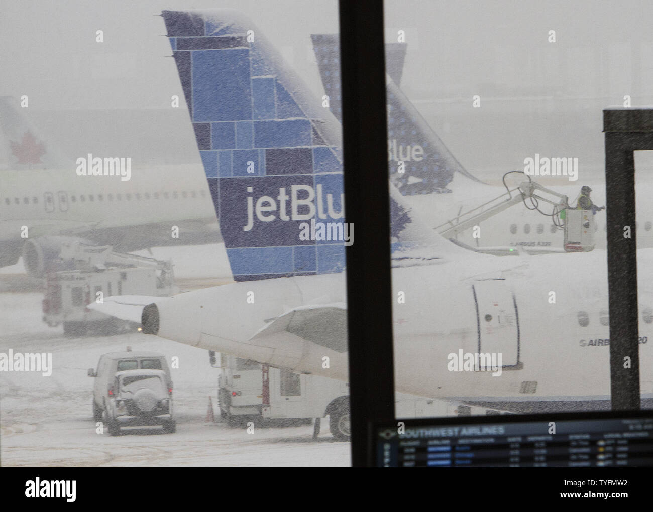 A de-icing crew moves among jetBlue aircraft at Newark Airport in Newark, New Jersey on February 3, 2014.  6-8 of inches of snow expected to fall in the tri-state area causes travel delays and cancellations.    UPI/Gary C. Caskey - Stock Image