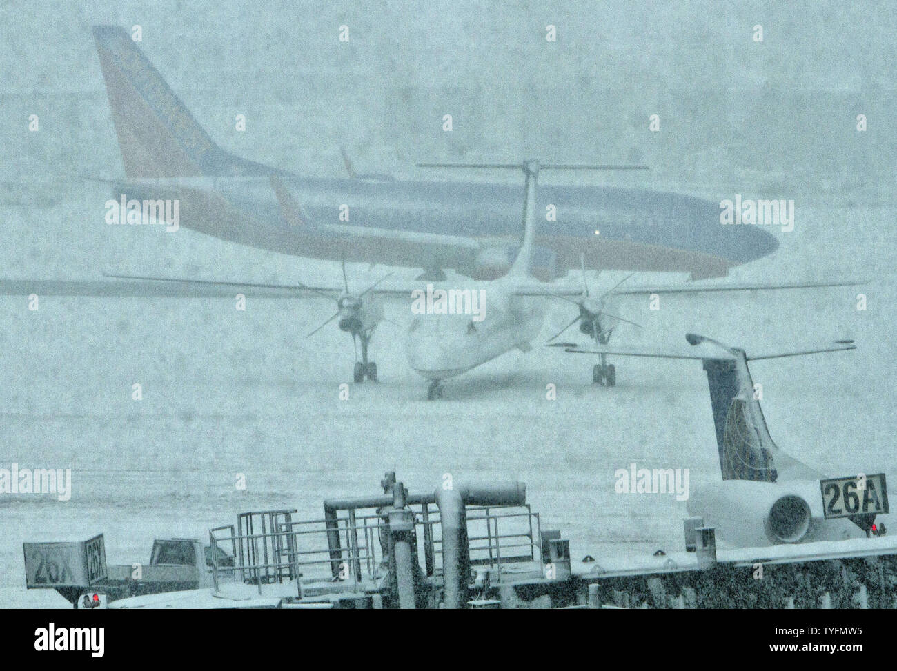 Aircraft sit unmoving during a snowstorm at Newark Airport in Newark, New Jersey on February 3, 2014.  6-8 of inches of snow expected to fall in the tri-state area causes travel delays and cancellations.    UPI/Gary C. Caskey - Stock Image