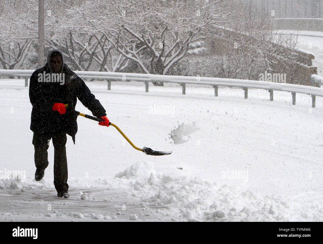 A airport worker continues clearing sidewalks for those arriving and departing the Air Train station at Newark Airport in Newark, New Jersey on February 3, 2014.  6-8 of inches of snow expected to fall in the tri-state area causes travel delays and cancellations.    UPI/Gary C. Caskey - Stock Image