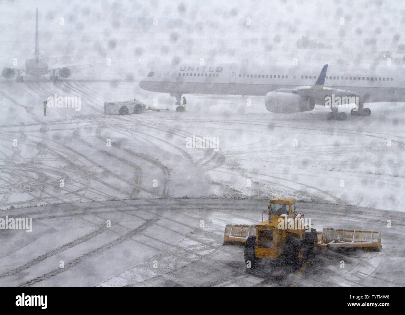 A snow removal plow begins to clear taxi areas of snowfall at Newark Airport in Newark, New Jersey on February 3, 2014.  6-8 of inches of snow expected to fall in the tri-state area causes travel delays and cancellations.    UPI/Gary C. Caskey - Stock Image