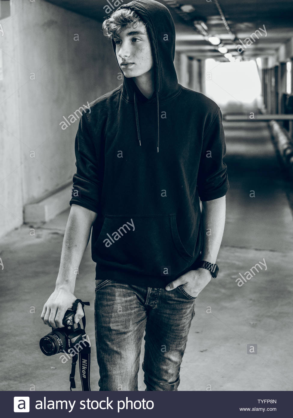 Medium shot BW young man with hoody holding camera in underground parking - Stock Image