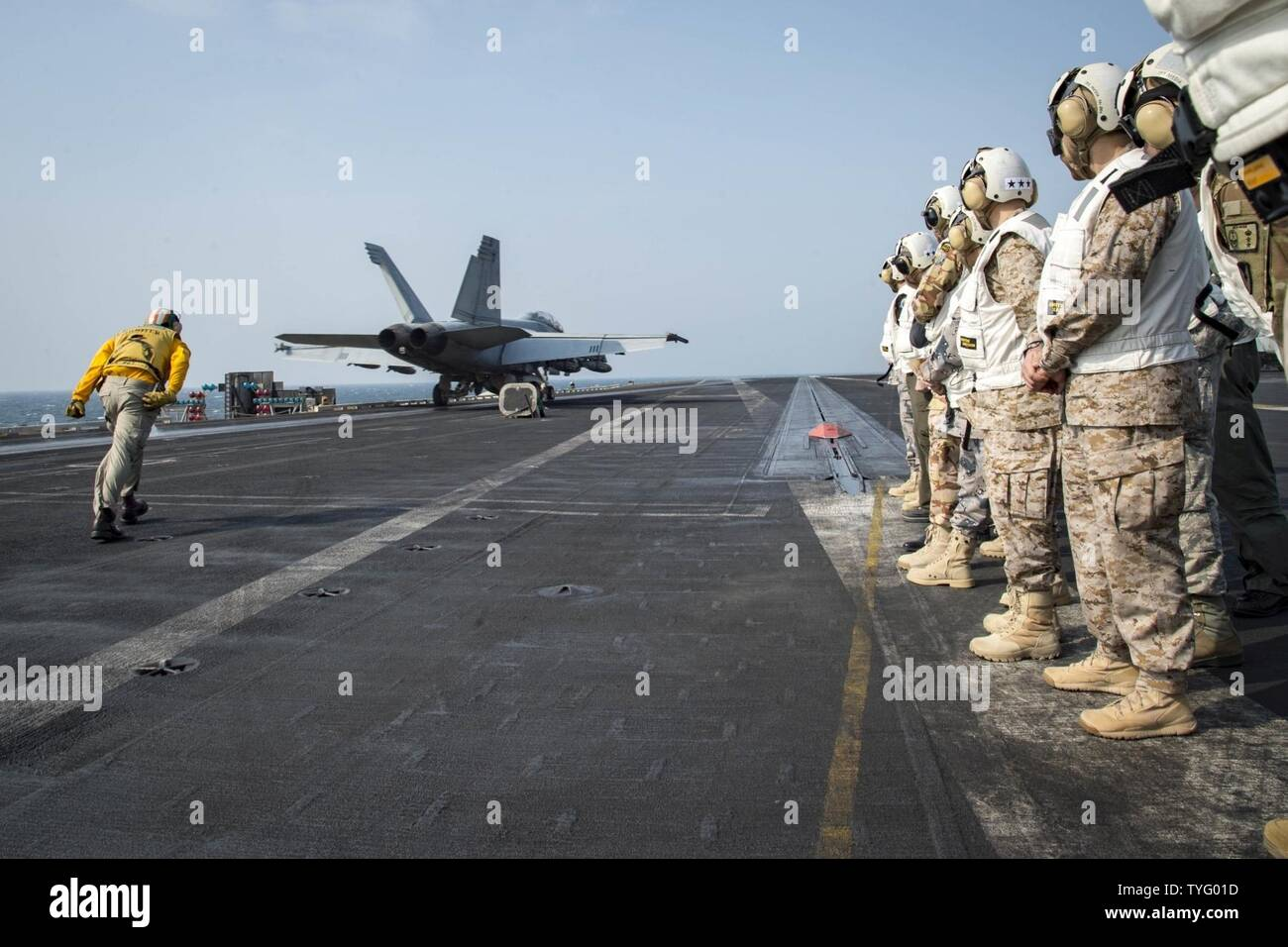 GULF (Nov. 7, 2016) Distinguished visitors observe flight operations during a theater security cooperation embark on the flight deck of the aircraft carrier USS Dwight D. Eisenhower (CVN 69) (Ike). Ike and its Carrier Strike Group are deployed in support of Operation Inherent Resolve, maritime security operations and theater security cooperation efforts in the U.S. 5th Fleet area of operations. - Stock Image