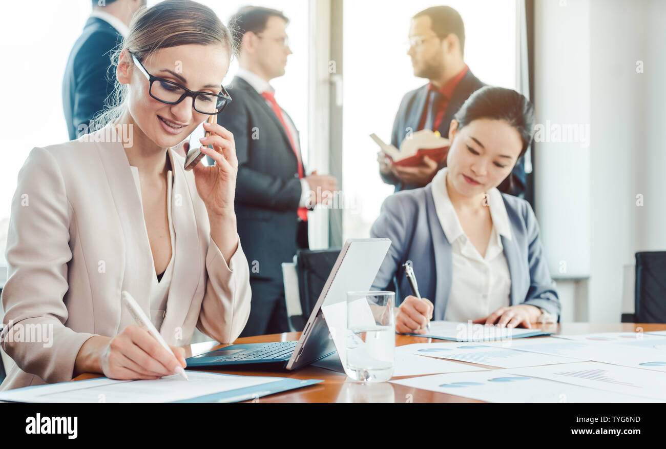 Business woman working while the men are chatting idly - Stock Image
