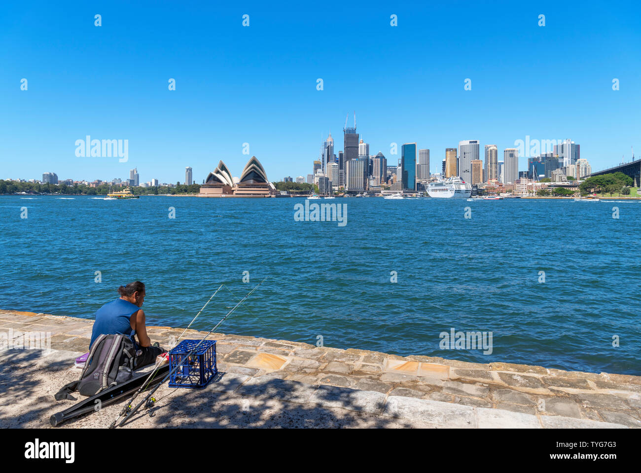 Angler fishing from the waterfront in Kirribilli in front of the Central Business District and Opera House, Sydney, New South Wales, Australia - Stock Image
