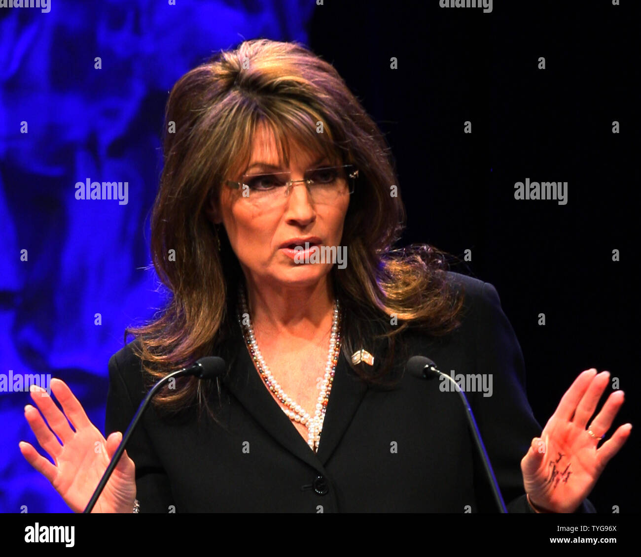Former Alaska Governor Sarah Palin speaks at the National Tea Party Convention at the Opryland Hotel in Nashville, Tennessee on February 6, 2010. The words 'energy', 'budget cuts', 'tax' and 'lift American spirits' are seen written in ink on her left hand. UPI/Terry Wyatt. - Stock Image