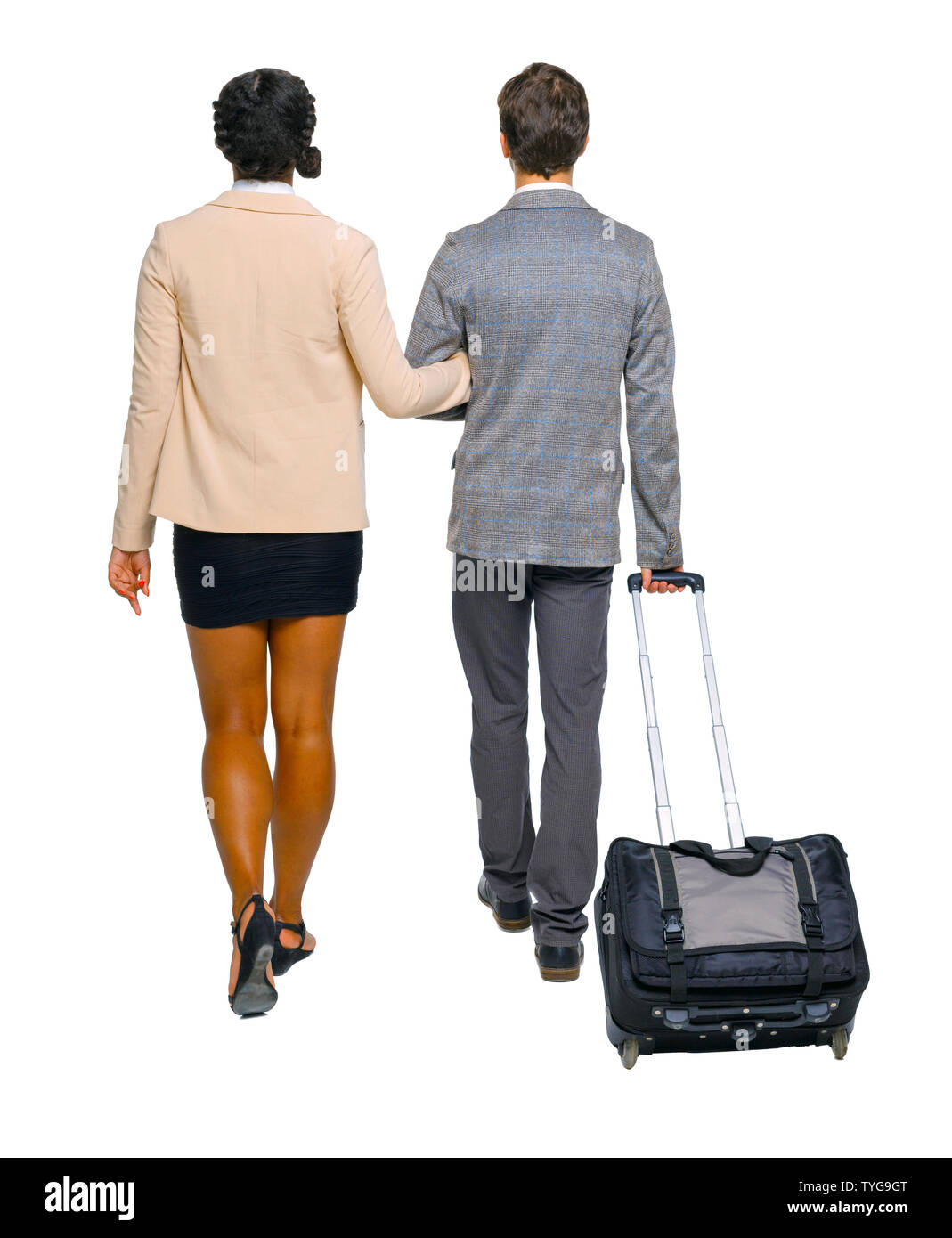 Back view of interracial going couple with suitcase. A guy in a suit leads his girlfriend by the arm. Rear view people collection. backside view of pe Stock Photo