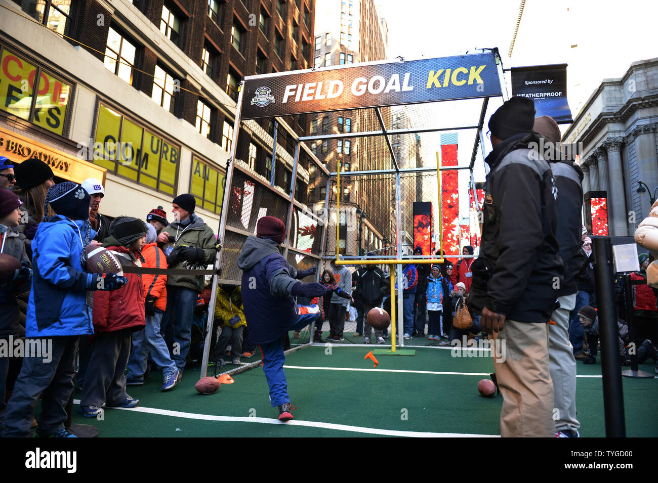 Young fans get a chance to kick a field goal near Times Square at the NFL Super Bowl Boulevard Fan Experience that takes up 13 blocks of Broadway in downtown Manhattan, New York on Wednesday, January 30, 2014.  Super Bowl XLVIII fans from the Denver Broncos and Seattle Seahawks fill the streets as they get read for the game on Sunday, February 2, 2014.  UPI/Pat Benic - Stock Image
