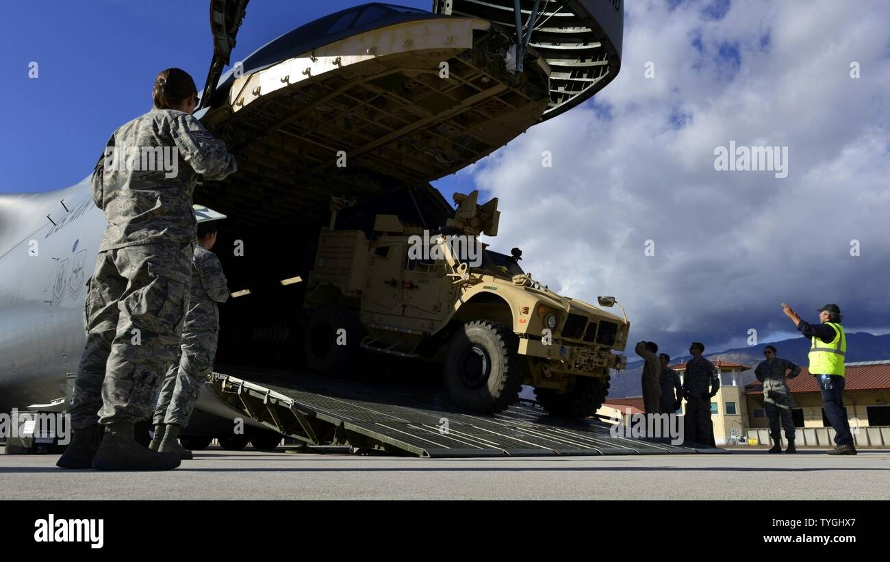 An all-terrain vehicle is backed into a C-5M Super Galaxy at Aviano Air Base, Italy on Nov. 8, 2016. The vehicles were transported to support operation efforts in Iraq. - Stock Image
