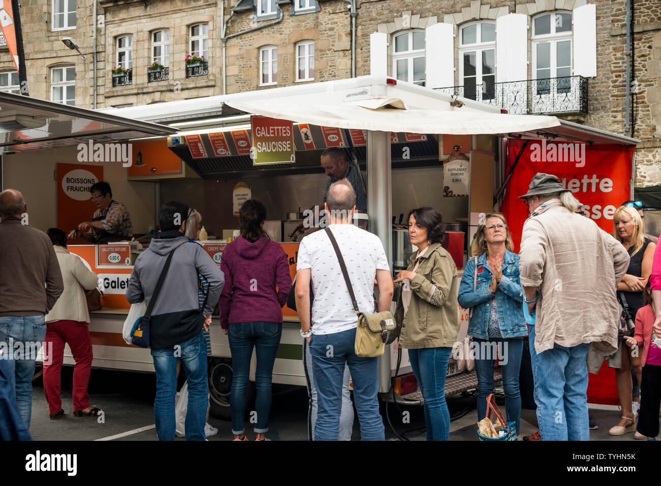 People queueing for galette saucisse (grilled sausage wrapped in crepe)  in the Thursday weekly Market in Dinan, Brittany, France Stock Photo