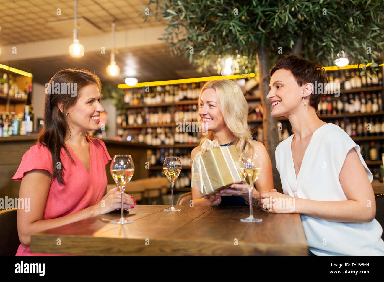 women giving present to friend at wine bar - Stock Image