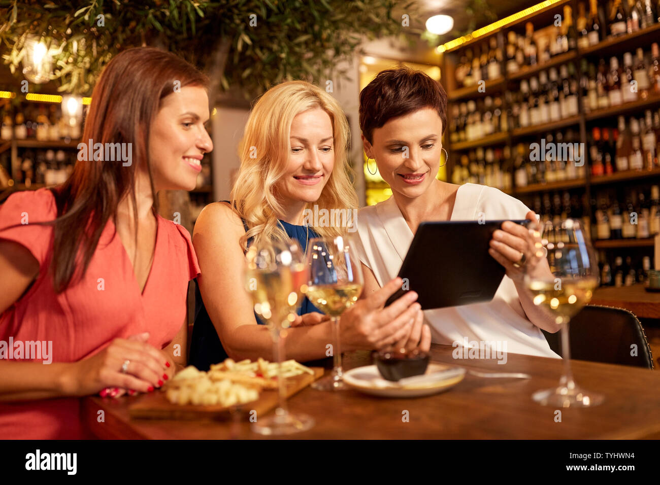 women with tablet pc at wine bar or restaurant - Stock Image