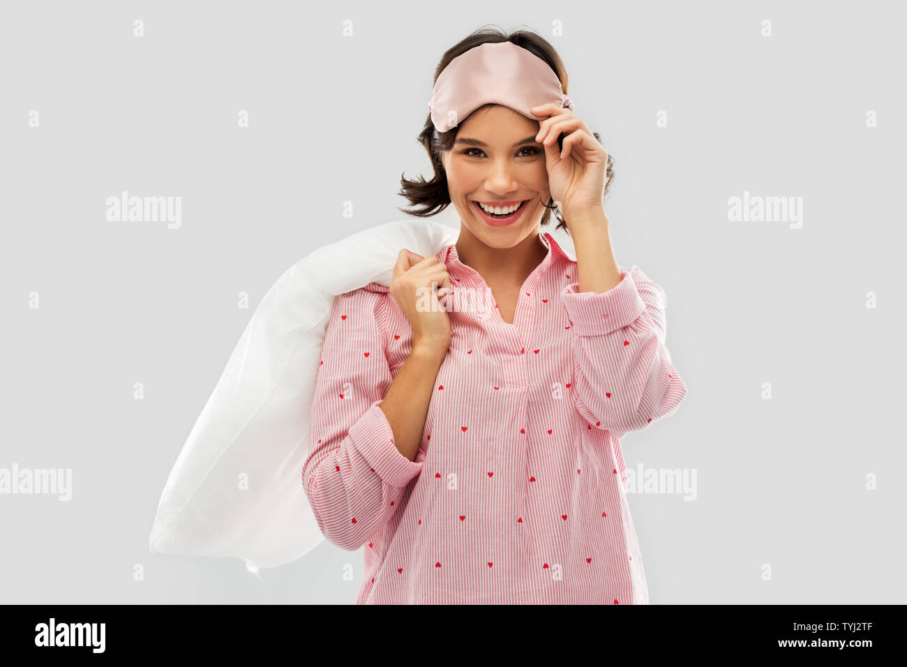 woman with pillow in pajama and eye sleeping mask - Stock Image