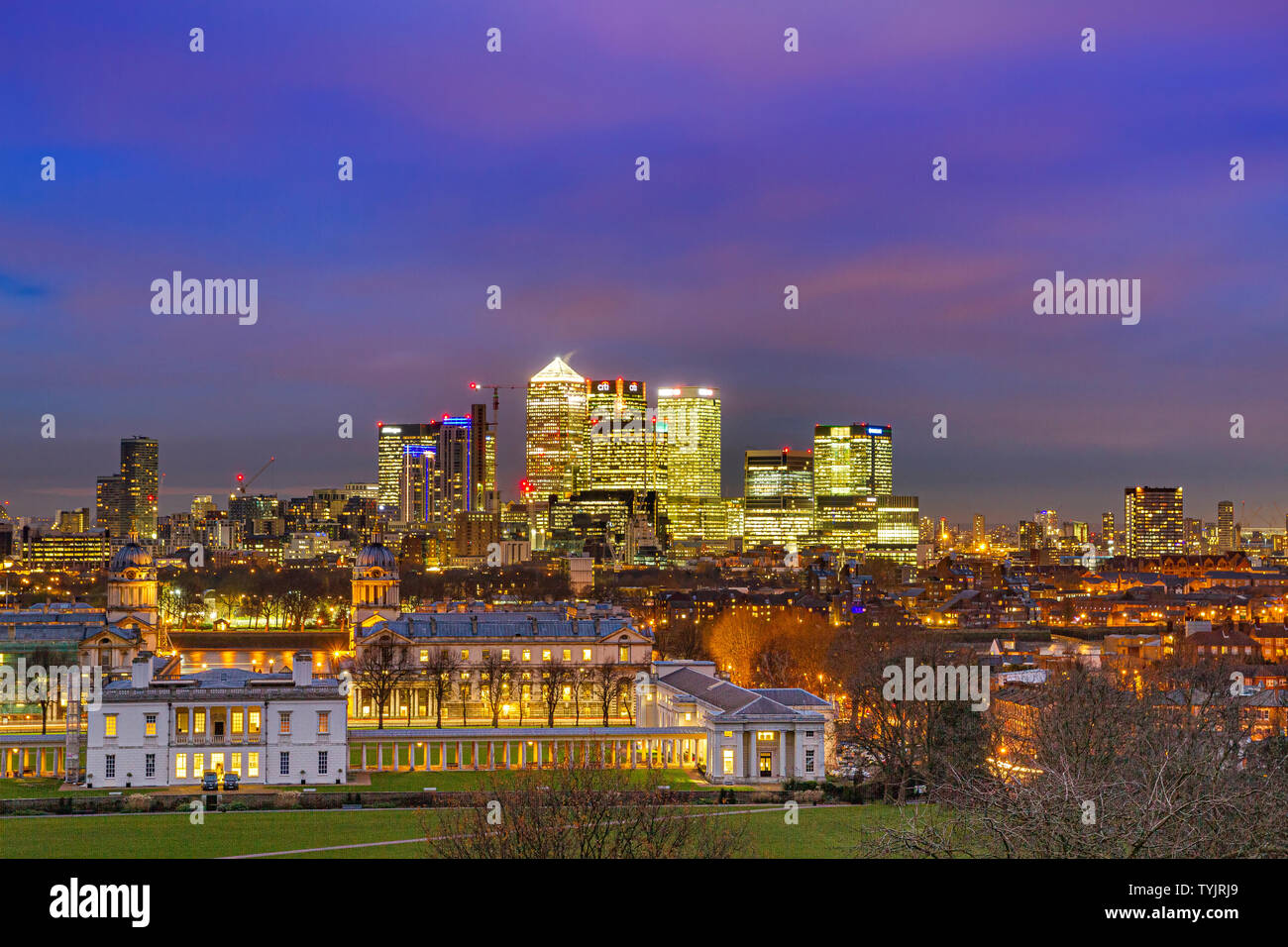 Night view of The Old Royal Naval College & National Maritime Museum with the towers of Canary Wharf in the background  from Greenwich Park ,London Stock Photo