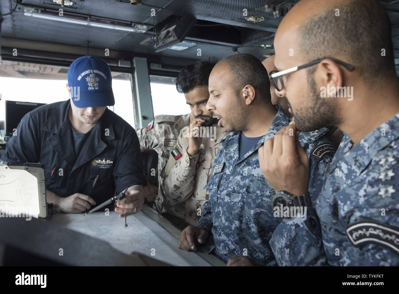 GULF (Nov. 14, 2016) Seaman Garret Cundiff, left, shows staff members from Combined Task Force (CTF) 152 how to plot a chart on the navigational bridge of the aircraft carrier USS Dwight D. Eisenhower (CVN 69) (Ike) during a theater security cooperation embark. Cundiff serves aboard Ike as a quartermaster. Ike and its Carrier Strike Group are deployed in support of Operation Inherent Resolve, maritime security operations and theater security cooperation efforts in the U.S. 5th Fleet area of operations. - Stock Image