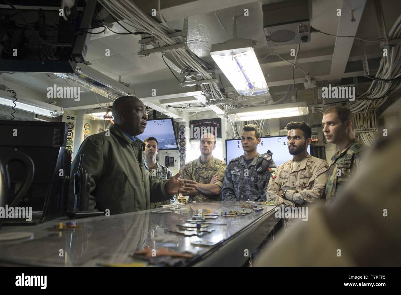 GULF (Nov. 14, 2016) Lt. Cmdr. Patrick Batiste, left, USS Dwight D. Eisenhower's (CVN 69) flight deck handling officer, speaks with staff members from Combined Task Force (CTF) 152 in the flight deck control room of the aircraft carrier during a theater security cooperation embark. The ship and its Carrier Strike Group are deployed in support of Operation Inherent Resolve, maritime security operations and theater security cooperation efforts in the U.S. 5th Fleet area of operations. - Stock Image