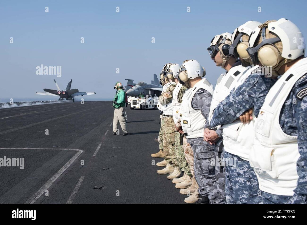 GULF (Nov. 14, 2016) Staff members from Combined Task Force (CTF) 152 observe operations on the flight deck of the aircraft carrier USS Dwight D. Eisenhower (CVN 69) (Ike) during a theater security cooperation embark. Ike and its Carrier Strike Group are deployed in support of Operation Inherent Resolve, maritime security operations and theater security cooperation efforts in the U.S. 5th Fleet area of operations. - Stock Image