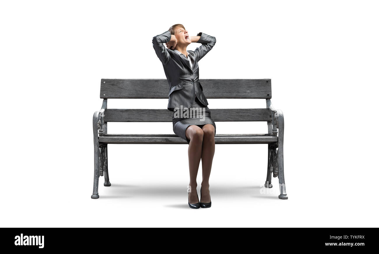 Stressful woman sitting on wooden bench. Screaming girl in business suit keeps hands on head. Pretty businesswoman in despair isolated on white backgr - Stock Image
