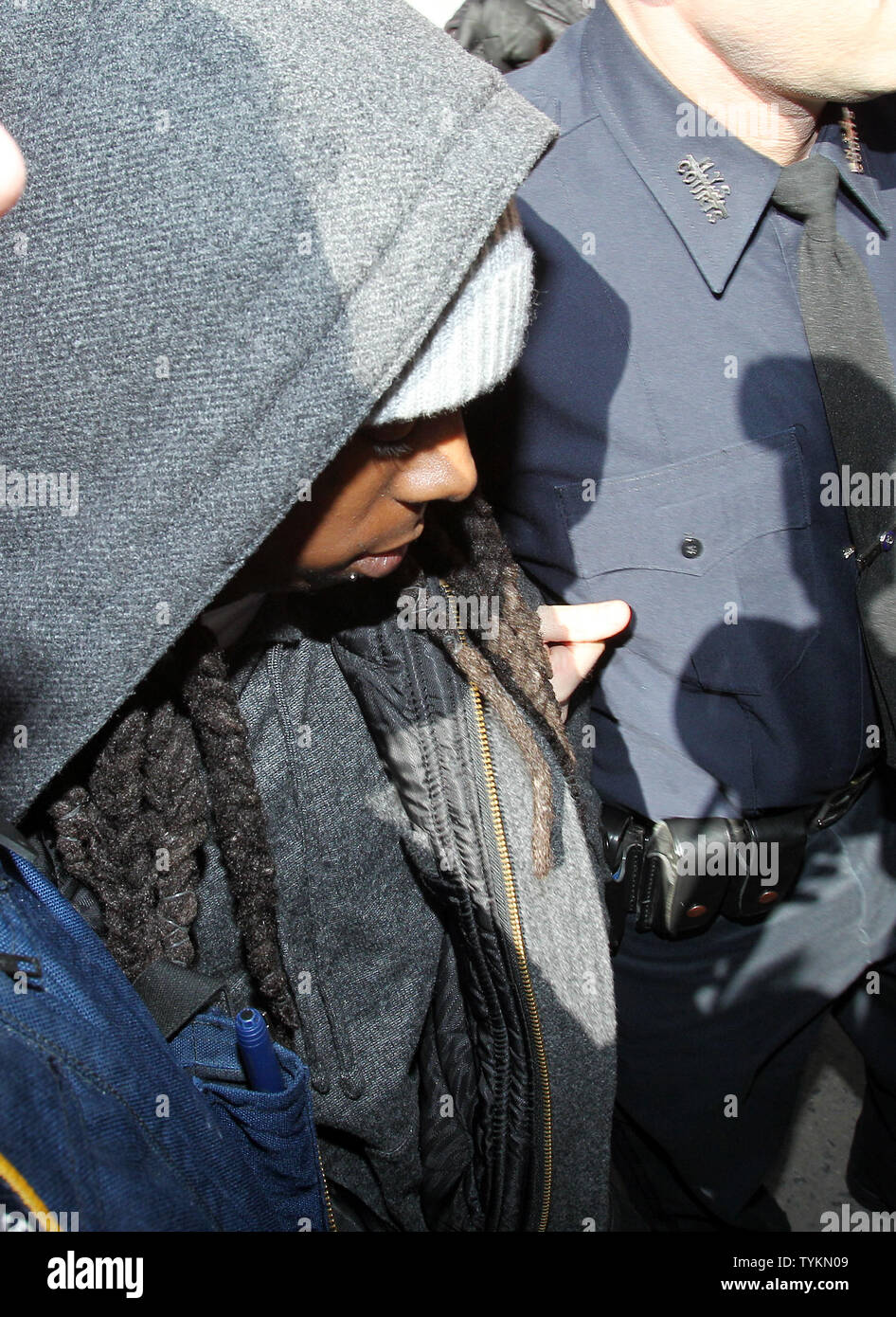 Lil Wayne is escorted into the Manhattan Criminal Court building at