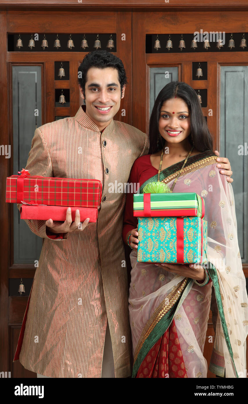 Indian Couple Standing In Front Of A Door With Gifts Stock Photo Alamy