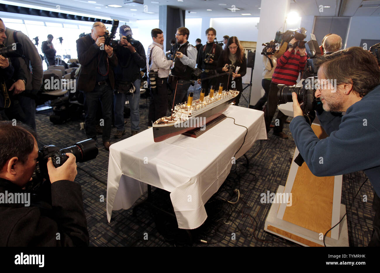 Media members gather around a model of the RMS Titanic as it sits on a table near where Artifacts recovered from the wreck site of the on display before being auctioned at the Intrepid Sea, Air & Space Museum in New York City on January 5, 2012. The auction will take place on April 11, 2012 on the 100 year anniversary of the ships maiden voyage and will be sold as one single collection.    UPI/John Angelillo - Stock Image