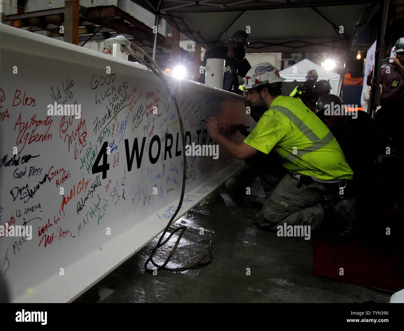 Construction workers sign the final steel beam before it is raised by crane to the top of 4 World Trade Center in New York City on June 25, 2012.   UPI/John Angelillo - Stock Image