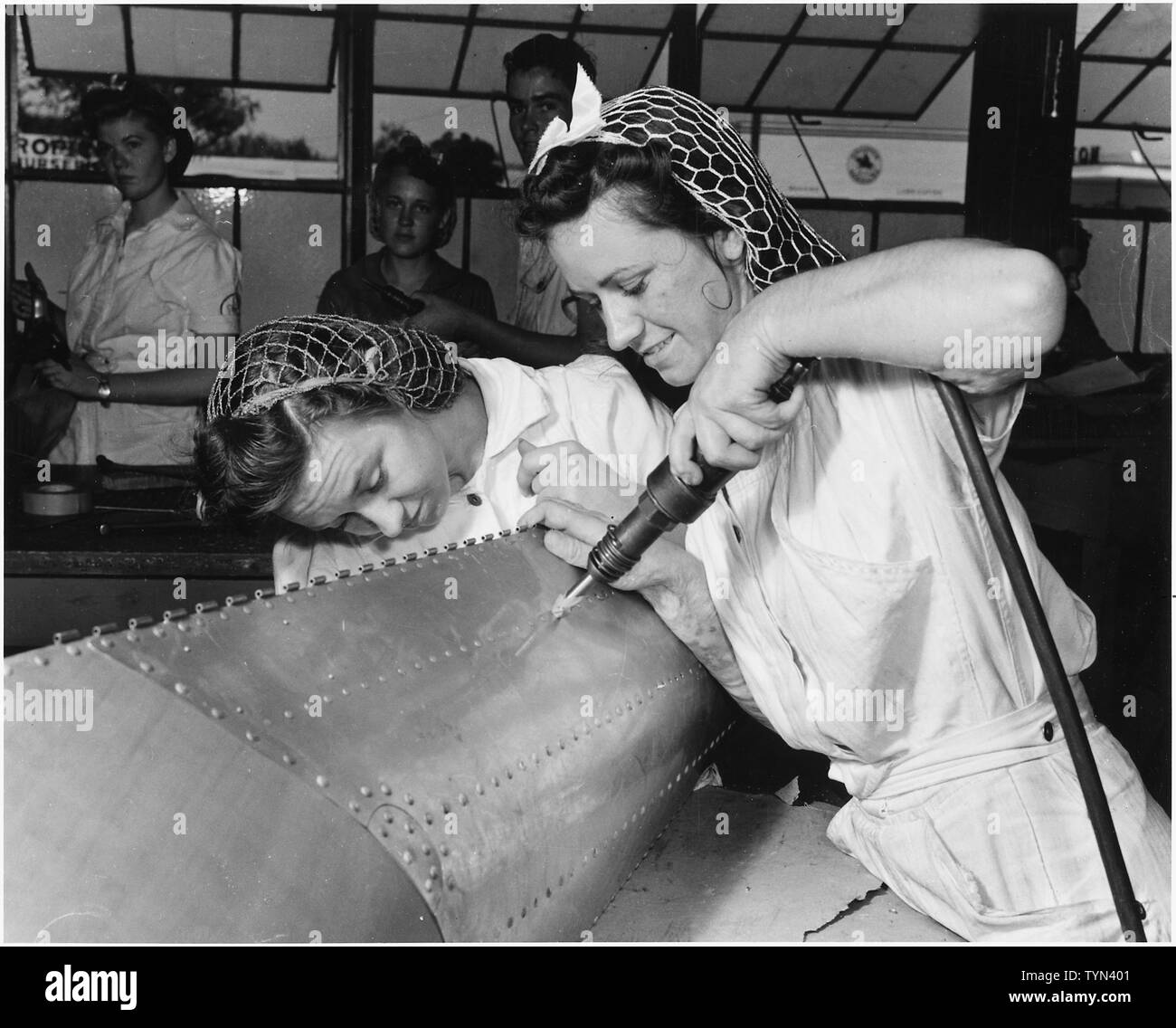 Two sisters who left the farm to keep our airmen flying. NYA trainees at the Corpus Christi, Texas, Naval Air Base, Evelyn and Lillian Buxkeurple are shown working on a practice bomb shell. - Stock Image