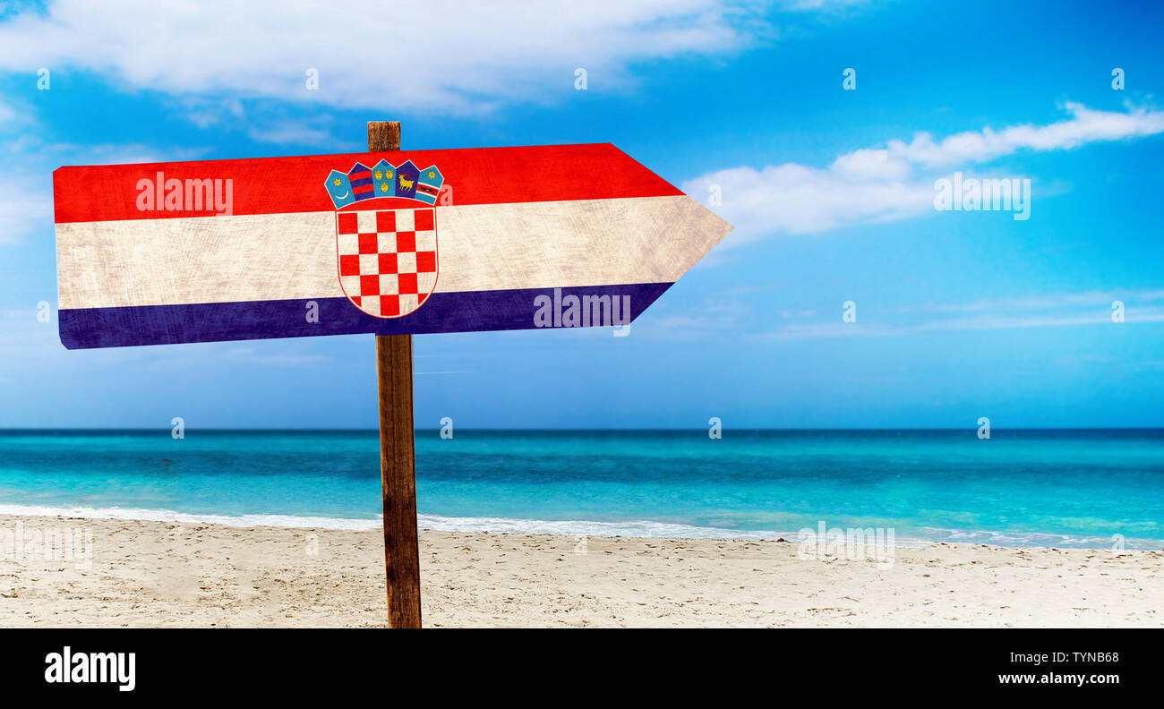 Croatia flag on wooden table sign on beach background. There is beach and clear water of sea and blue sky in the background. Stock Photo