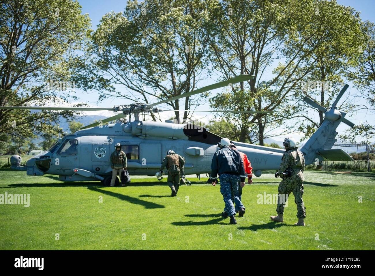 KAIKOURA, New Zealand (Nov. 18, 2016) Winston Gray, the mayor of Kaikoura, accompanied by Cmdr. Timothy LaBenz, commanding officer of USS Sampson (DDG 102), prepares to embark an MH-60R Sea Hawk, attached to Helicopter Maritime Strike Squadron (HSM) 73, to conduct an aerial survey of damage in the area. HSM-73 is operating from Sampson, which at the request of the government of New Zealand, remains off the coast of New Zealand's South Island to offer assistance to those affected by the recent earthquake. (New Zealand Defence Force - Stock Image