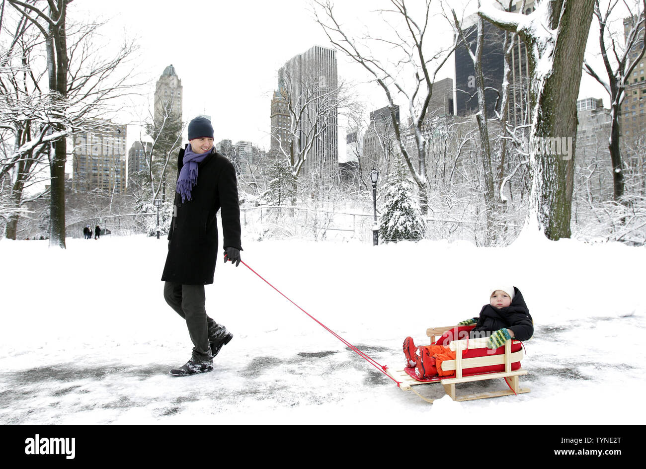 A man pulls a child through Central Park after winter storm