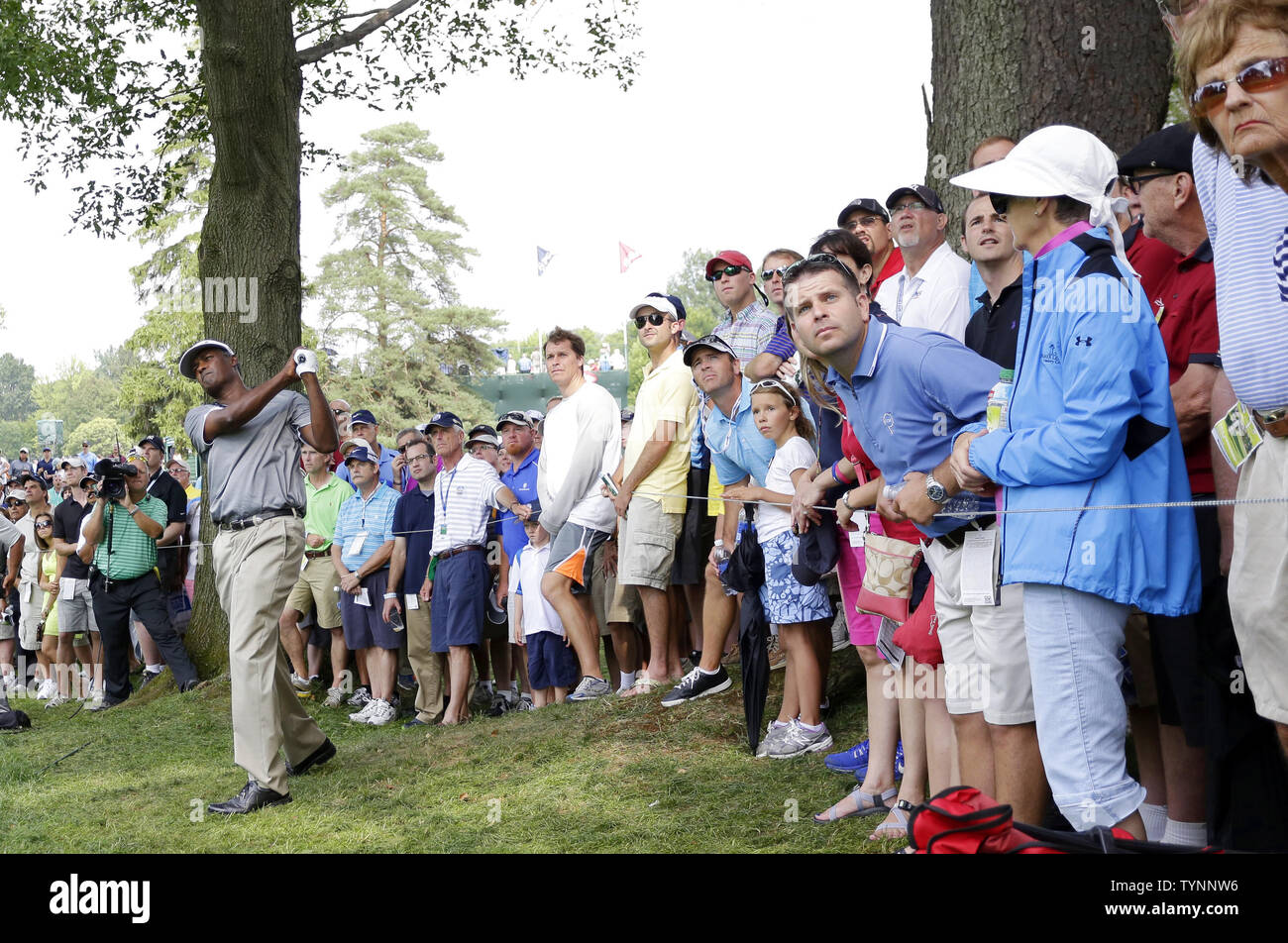 Fans watch Vijay Singh hit out of the rough on the 9th hole in the