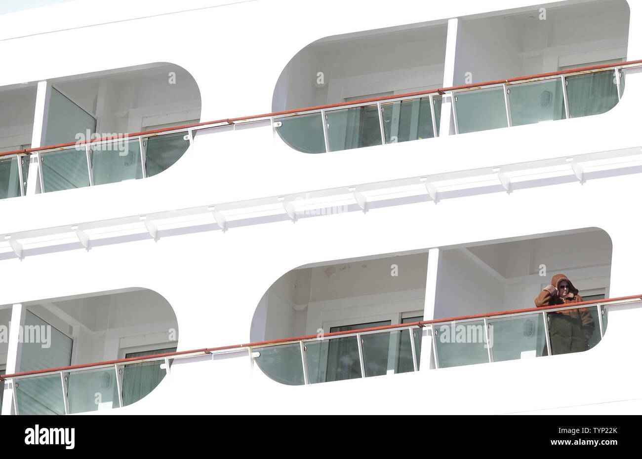 A passenger stands on a balcony of a Royal Caribbean Liner as it docks in  Bayonne,