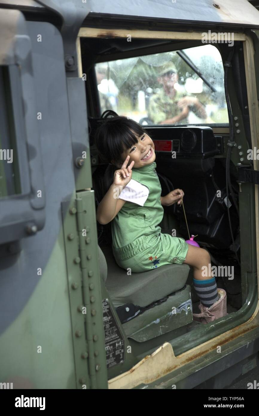 An Okinawa resident poses inside a Humvee Nov. 20, 2016 during the Japan Ground Self Defense Force Festival on Camp Naha, Okinawa, Japan. The festival celebrated the 6th anniversary of the 15th Brigade and the 44th anniversary of Camp Naha. Marines with Combat Assault Battalion, 3rd Marine Division, III Marine Expeditionary Force brought the Humvee, a Light Armored Vehicle and an Assault Amphibious Vehicle for display. Attendees of the festival were able to take photos with the Marines and their vehicles. Stock Photo