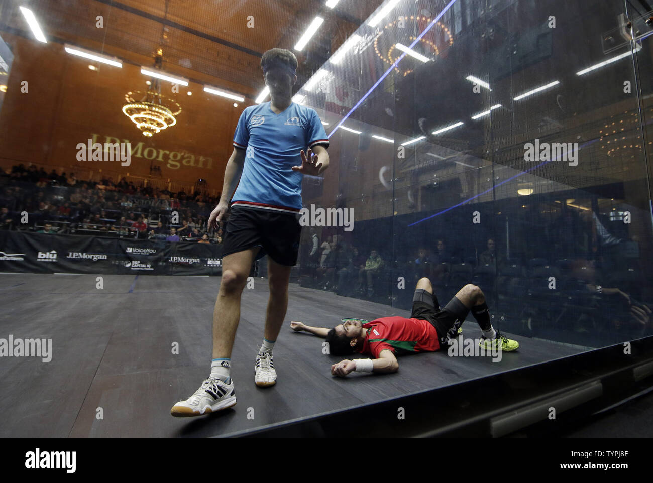 Chris Simpson of England walks by Cesar Salazar of Mexico who falls down falls to the court during a point at JPMorgan Chase & Co.'s 18th annual  'Tournament of Champions' Professional Squash Tournament in Grand Central Terminal in New York City on January 16, 2015. The annual tournament is scheduled to continue through January 23rd.       Photo by John Angelillo/UPI - Stock Image