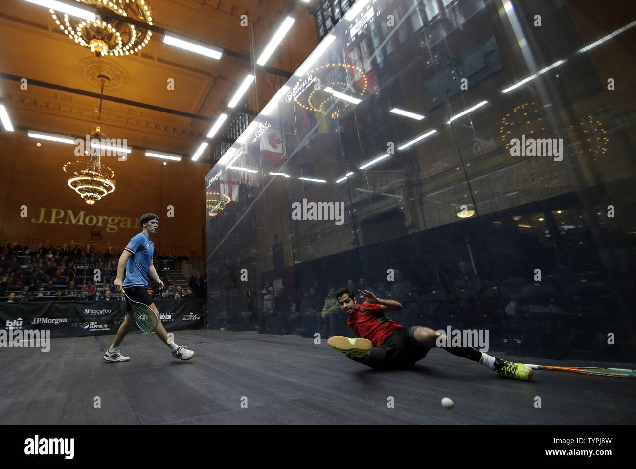 Chris Simpson of England watches Cesar Salazar of Mexico land on the court after diving for a ball at JPMorgan Chase & Co.'s 18th annual  'Tournament of Champions' Professional Squash Tournament in Grand Central Terminal in New York City on January 16, 2015. The annual tournament is scheduled to continue through January 23rd.       Photo by John Angelillo/UPI - Stock Image