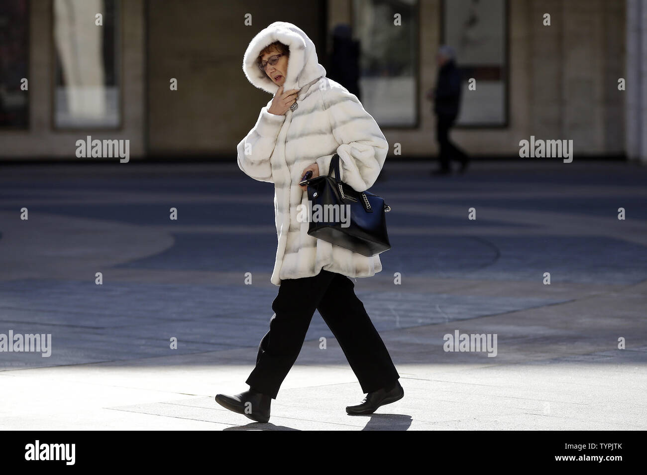 A woman bundled up for freezing cold weather walks around the grounds at Lincoln Center during the week of Mercedes-Benz Fashion Week Fall 2015 in New York City on February 13, 2015. Temperatures fell into the teens in New York with snow expected tomorrow through Sunday.      Photo by John Angelillo/UPI - Stock Image