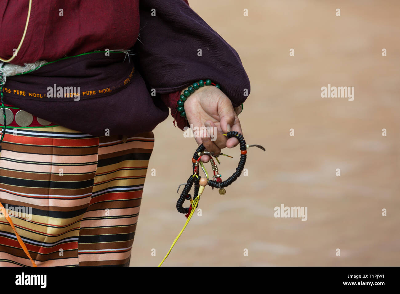 close up of a women, wearing traditional Tibetan clothes, and holds a prayers chain in her hand - Stock Image
