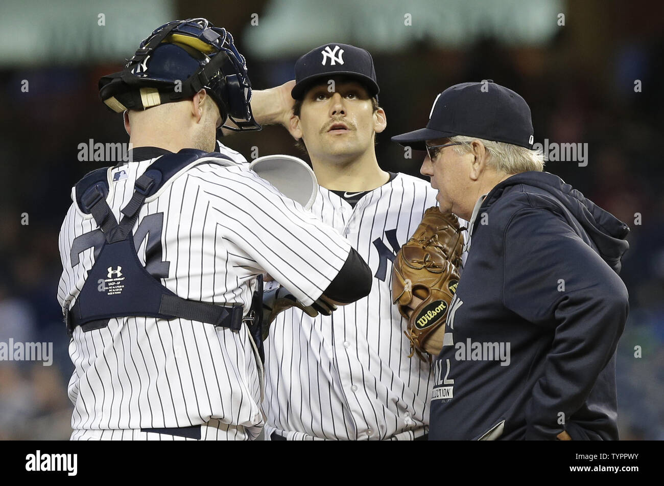New York Yankees starting pitcher Nathan Eovaldi stands with Brian McCann and coach Larry Rothschild in the 2nd inning against the Baltimore Orioles at Yankee Stadium in New York City on May 7, 2015.      Photo by John Angelillo/UPI - Stock Image