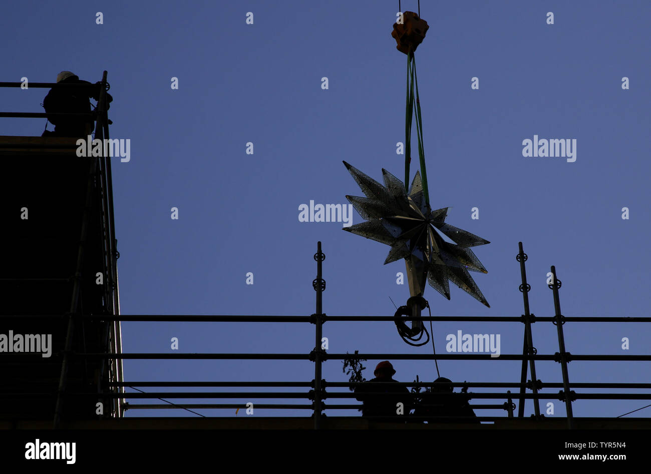Workers help position The Swarovski Star when it is raised by crane to the top of the world-famous Rockefeller Center Christmas tree on November 16, 2015 in New York City. 2015 marks the 12th year the Swarovski Star will adorn the Rockefeller Center Christmas tree. The Star is comprised of 25,000 crystals, with one million facets, and measures 9 and 1/2 feet in diameter and 1 1/2 feet deep. The Star weighs 550 pounds, including 300 pounds of crystal panels, and is composed of six outer rays and six smaller inner rays.       Photo by John Angelillo/UPI Stock Photo