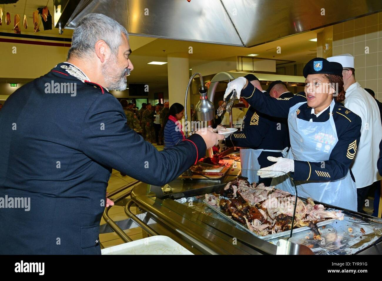 U.S. Army Master Sgt. Nicola M. Felder, assigned to U.S. Army Africa, serves lunch to Capt. Francesco Provvidenza, company commander Carabinieri Southern European Task Force, during the Thanksgiving lunch celebration at Caserma Del Din in Vicenza, Italy, Nov. 22, 2016. - Stock Image