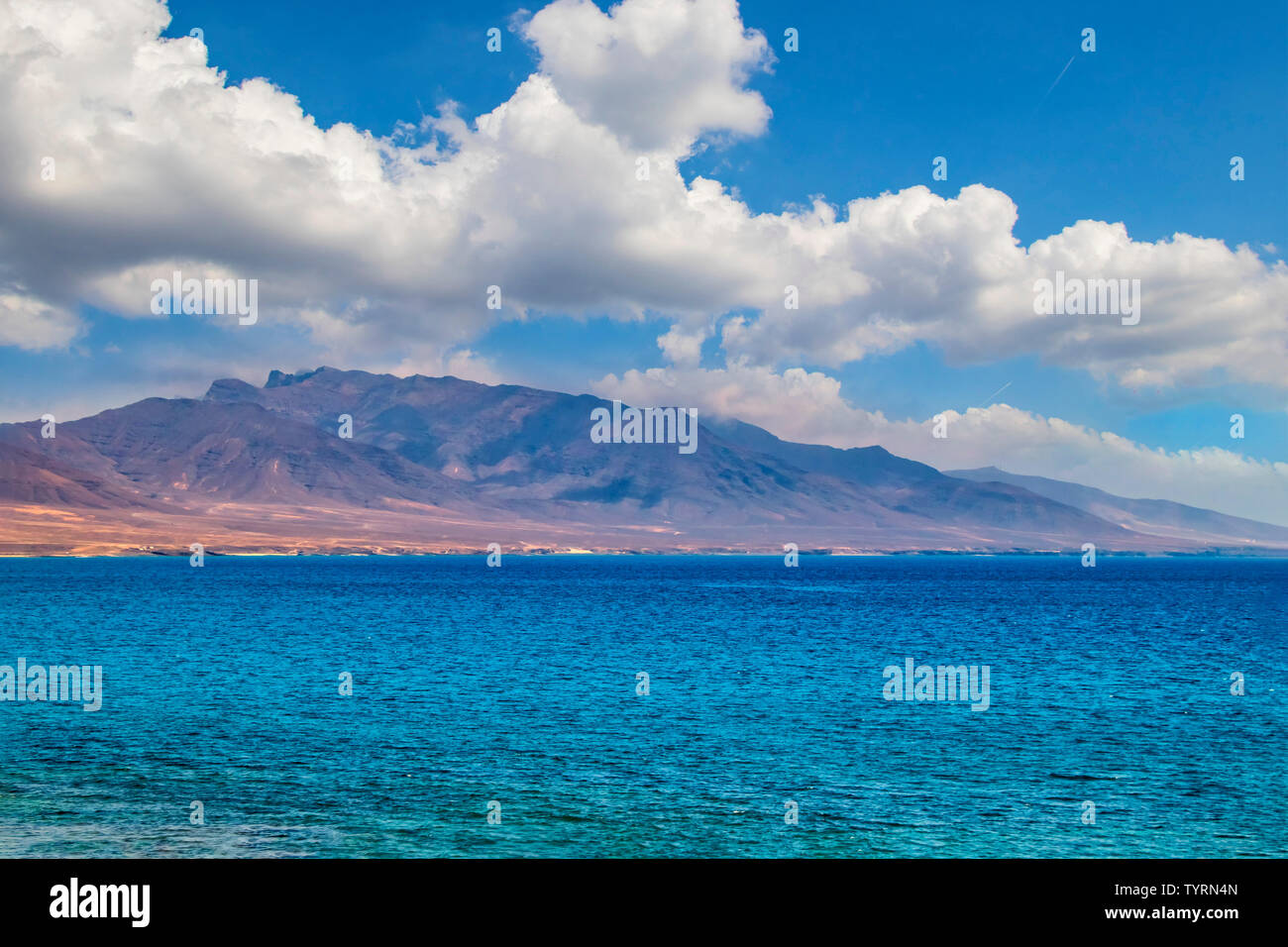View of the hill on the island Fuerteventura near Morro Jable, Canary islands, Spain. There is clear blue water and beautiful sky. Stock Photo