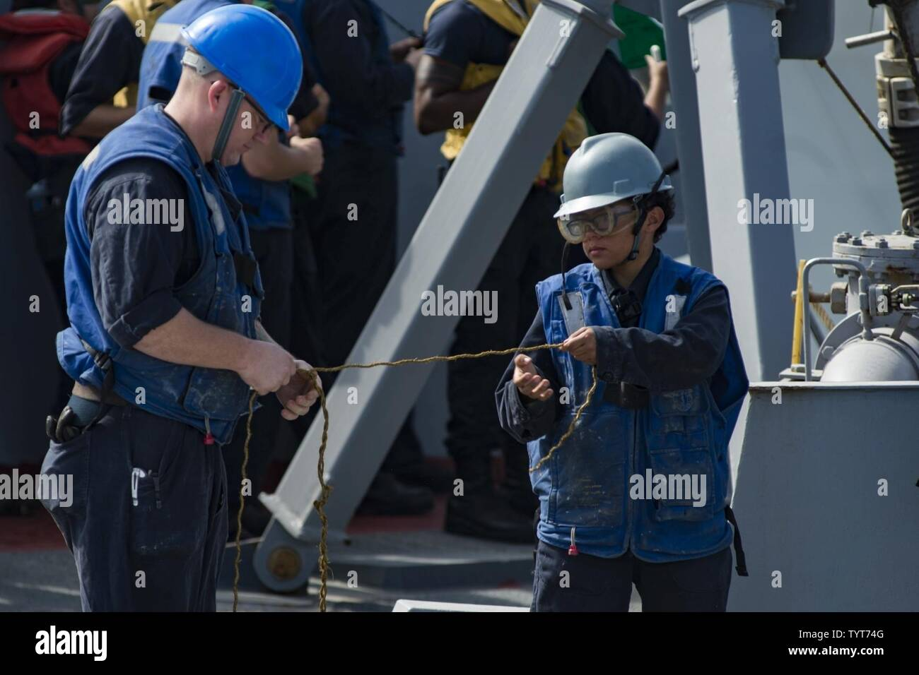 SEA (Nov. 25, 2016) Petty Officer 1st Class James Norskow, left, and Seaman Vanessa Verges, assigned to the guided-missile destroyer USS Nitze (DDG 94), unravel a line during an underway replenishment with the dry cargo and ammunition ship USNS Alan Shepard (T-AKE 3). Nitze, deployed as part of the Eisenhower Carrier Strike Group, is supporting maritime security operations and theater security cooperation efforts in the U.S. 5th Fleet area of operations. - Stock Image