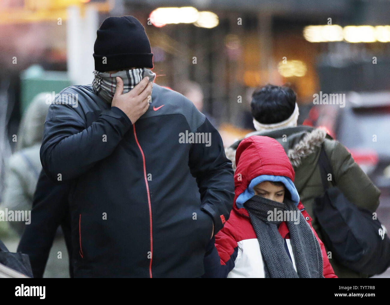 A man with a scarf over his face walks with a child in lower Manhattan in below freezing temperature in New York City on January 2, 2018. The New York City area will remain dangerously cold this week as at least two inches of snow are expected to fall on Wednesday and Thursday.     Photo by John Angelillo/UPI - Stock Image