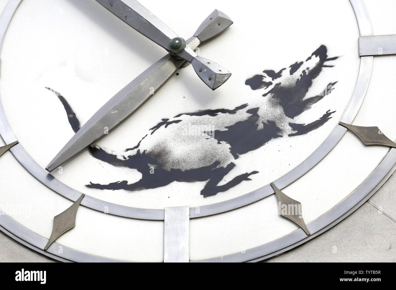 A painting of a rat running in a street clock face like a