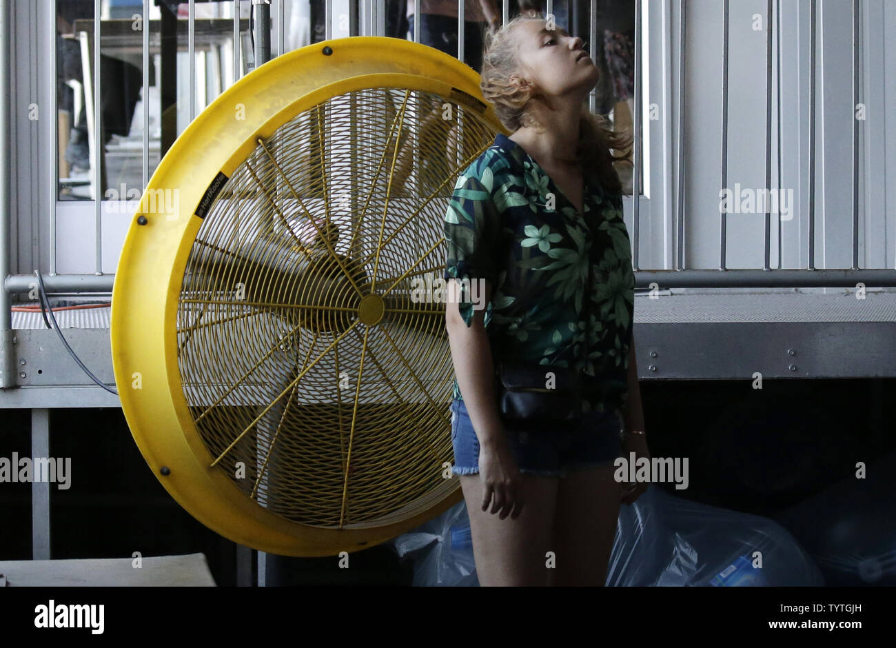A girl cools off at a fan in temperatures above 95 degrees before boarding a ferry to Liberty Island 2 days before Independence Day and the 4th of July in New York City on July 2, 2018. Temperatures have topped 90 degrees for a fourth straight day in New York City on Monday extending the city's heat wave.     Photo by John Angelillo/UPI Stock Photo