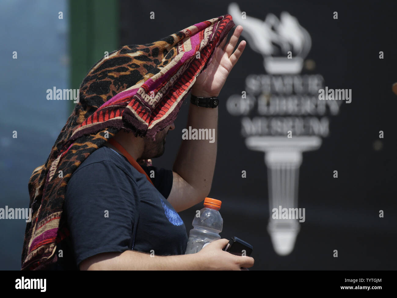 A man covers his head to seek protection from the sun in temperatures above 95 degrees on Liberty Island 2 days before Independence Day and the 4th of July in New York City on July 2, 2018. Temperatures have topped 90 degrees for a fourth straight day in New York City on Monday extending the city's heat wave.     Photo by John Angelillo/UPI Stock Photo