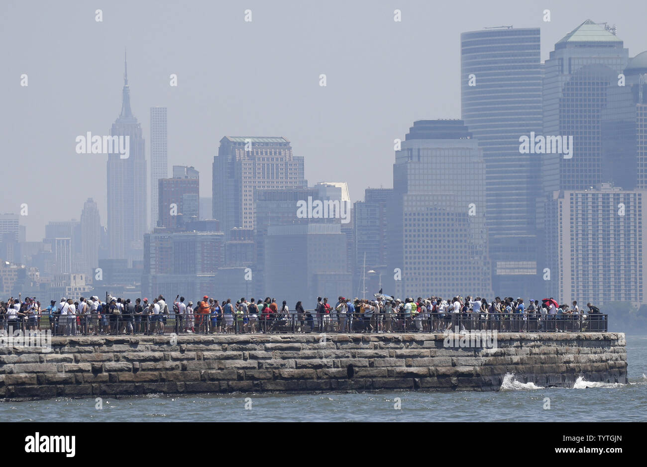 Tourists stand on Liberty Island with a view of The Statue of Liberty and Manhatan 2 days before Independence Day and the 4th of July in New York City on July 2, 2018.      Photo by John Angelillo/UPI Stock Photo