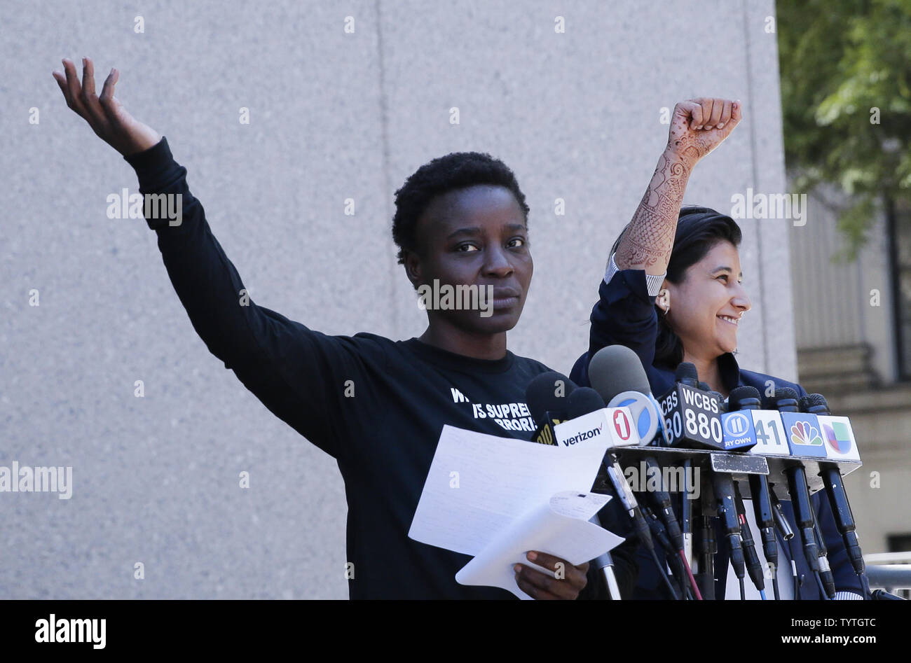Statue Of Liberty climber and Rise and Resist protester Therese Okoumou raises her hand with Attorney Rhiya Trivedi when she speaks after exiting Court in New York City on July 5, 2018 in New York City. The woman who partially climbed up the Statue of Liberty on July 4th Independence Day and prompted authorities to evacuate Liberty Island was released without bail, and if convicted would face up to six months behind bars.    Photo by John Angelillo/UPI Stock Photo