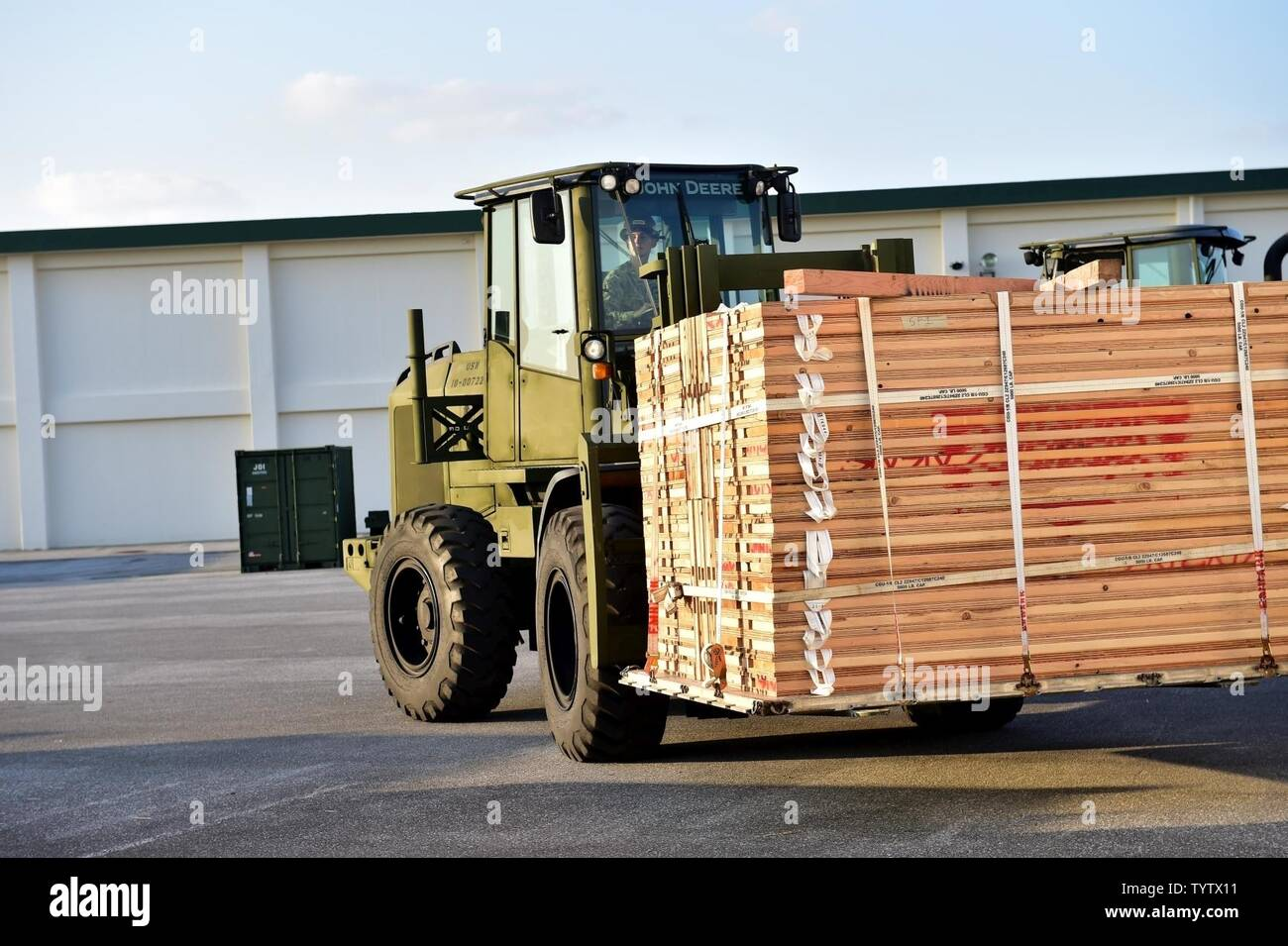 OKINAWA, Japan (Nov. 29, 2016) Seaman Miranda Roudabush. assigned to Naval Mobile Construction Battalion (NMCB) 5, drives a forklift while moving pallets of wood outside of a warehouse on Camp Shields during an embark exercise. The exercise tests the commands ability to mobilize within 48 hours to react to different types of contingency operations around the world. NMCB 5 is the forward deployed Western Pacific NMCB ready to support Major Combat Operations, Humanitarian Assistance and Disaster Relief operations, and to provide general engineering and civil support to Navy, Marine Corps and joi - Stock Image